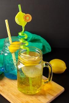 Uma vista frontal coquetel de limão bebida fresca fresca dentro de copos de vidro fatias e limões inteiros palhas coloridas sobre o fundo escuro coquetel de frutas