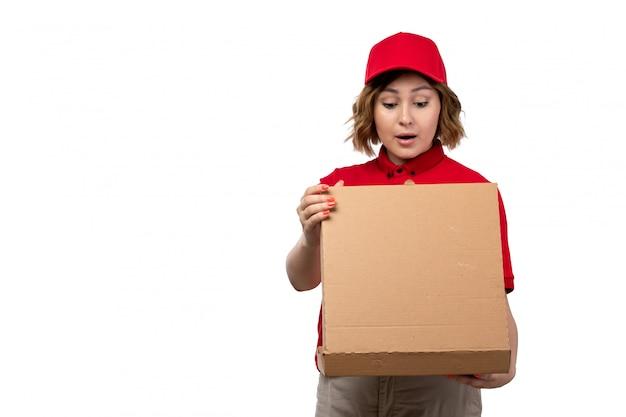 Uma vista frontal correio feminino jovem trabalhadora do serviço de entrega de comida segurando a caixa de entrega de comida abrindo-o em branco