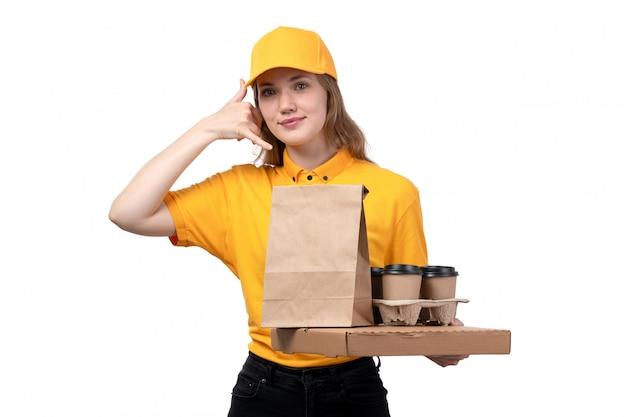 Uma vista frontal correio feminino jovem trabalhadora do serviço de entrega de comida sorrindo segurando caixas de entrega de comida e mostrando um sinal de chamada em branco