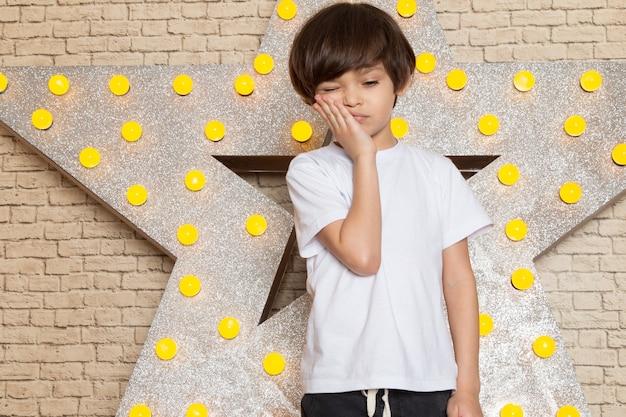 Uma vista frontal criança bonitinha em jeans escuros de camiseta branca na estrela projetado carrinho amarelo e luz de fundo