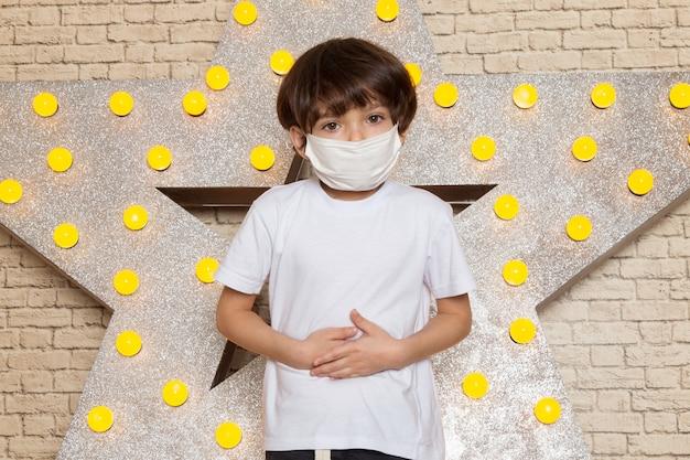 Uma vista frontal criança bonitinha em t-shirt branca calça jeans escura máscara branca estéril na estrela projetado carrinho amarelo e luz de fundo