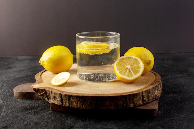 Uma vista frontal da água com uma bebida fresca de limão com limões fatiados e limões inteiros dentro de vidros transparentes no escuro