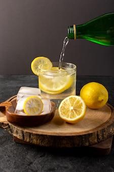Uma vista frontal de água com bebida fresca de limão dentro de vidro derramando com cubos de gelo com limões fatiados no escuro