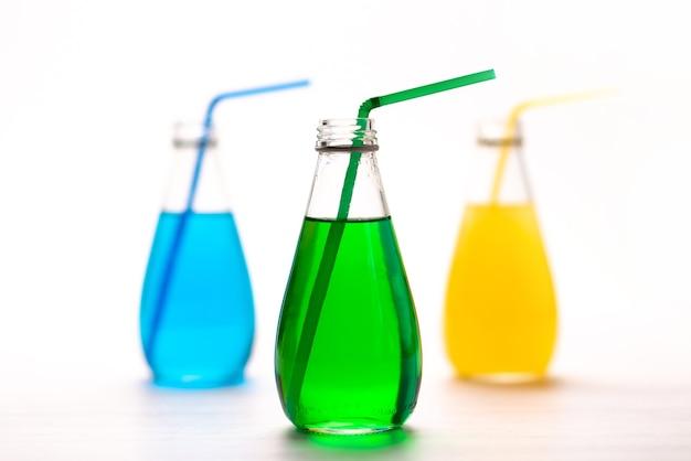 Uma vista frontal de bebidas coloridas com cobertura e refrescante canudos em branco, beber coquetel de suco de cor