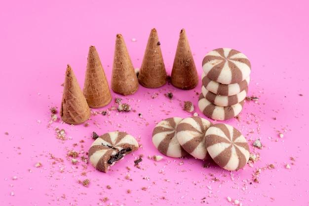 Uma vista frontal de biscoitos de chocolate junto com chifres na cor rosa, biscoito biscoito doce