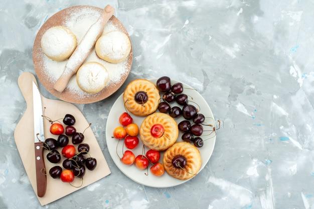 Uma vista frontal de biscoitos saborosos com cerejas dentro do prato e biscoito de massa