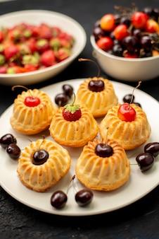 Uma vista frontal de biscoitos saborosos dentro de um prato branco com morangos e cerejas no bolo de biscoito de frutas escuro