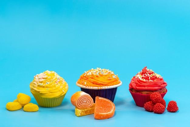 Uma vista frontal de bolinhos coloridos com geleias em azul, bala de biscoito