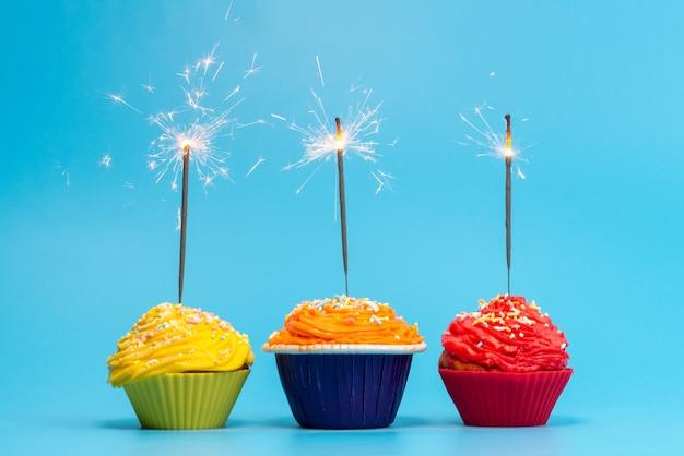 Uma vista frontal de bolinhos coloridos deliciosos isolados no azul, cor de festa de biscoito