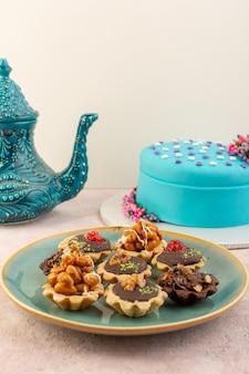 Uma vista frontal de bolinhos de chocolate dentro de um prato com um bolo de aniversário azul na mesa rosa