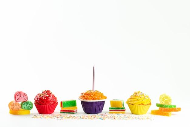 Uma vista frontal de bolos coloridos junto com doces de geleia em branco, cor de açúcar confiture