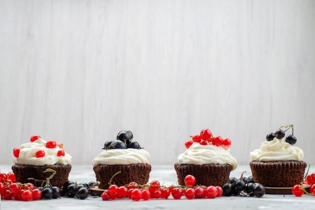 Uma vista frontal de bolos de chocolate projetados com creme de frutas na mesa branca