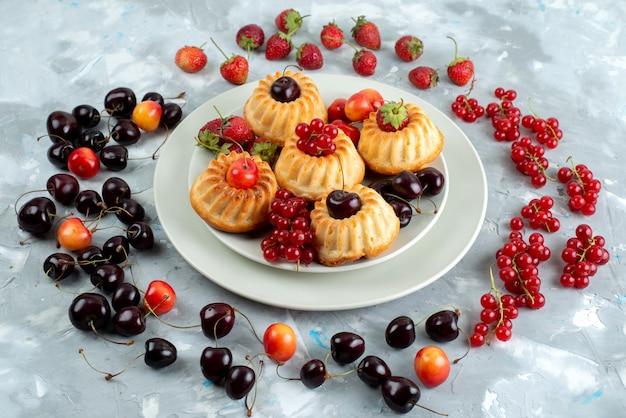 Uma vista frontal de bolos deliciosos com frutas vermelhas suaves e suculentas dentro de um prato branco sobre o bolo de frutas de baga da mesa de luz