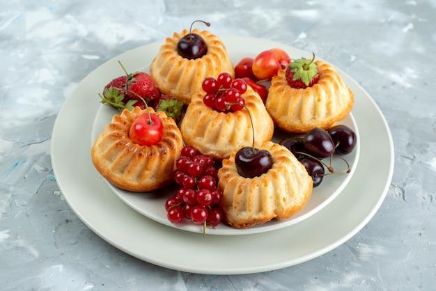 Uma vista frontal de bolos deliciosos com frutas vermelhas suaves e suculentas dentro de um prato branco sobre o bolo de frutas de mesa leve