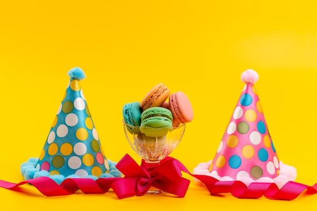 Uma vista frontal de bonés de aniversário junto com macarons franceses isolados na celebração de aniversário de açúcar amarelo
