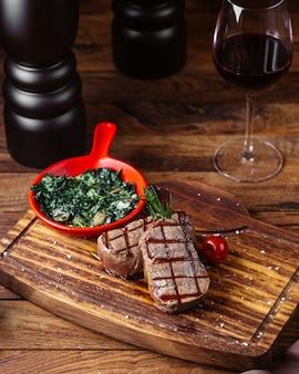 Uma vista frontal de carne frita com molho e verduras junto com um copo de vinho na mesa marrom.