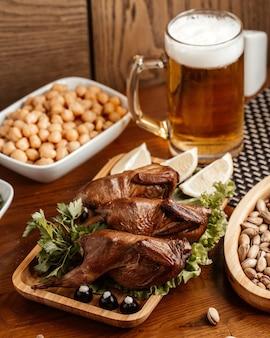 Uma vista frontal de carne frita com nozes, amendoim e cerveja na mesa marrom.