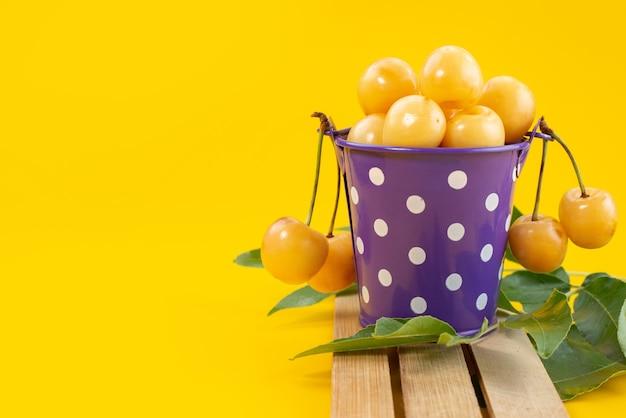 Uma vista frontal de cerejas amarelas suaves e doces dentro de uma cesta roxa em uma mesa de madeira e frutas amarelas no verão