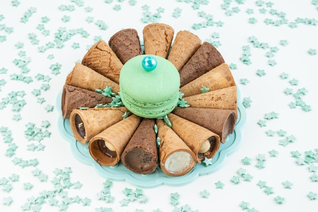 Uma vista frontal de chifres de sorvete com macaron francês verde no branco, sobremesa de biscoito de bolo
