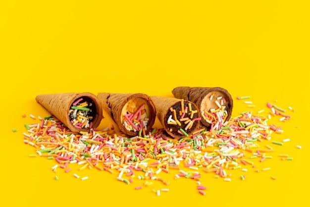 Uma vista frontal de chifres de sorvete com partículas de doces coloridos em amarelo, chifre de cor açúcar doce