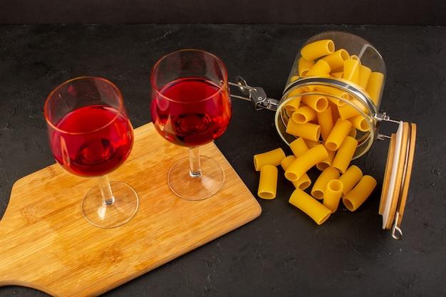 Uma vista frontal de copos de vinho em uma mesa de madeira marrom junto com massa italiana crua na mesa escura