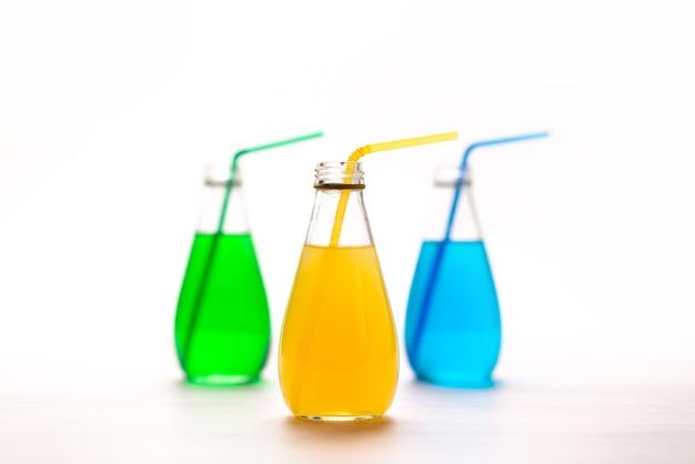 Uma vista frontal de coquetéis coloridos com canudos em branco, beber suco de cor de coquetel