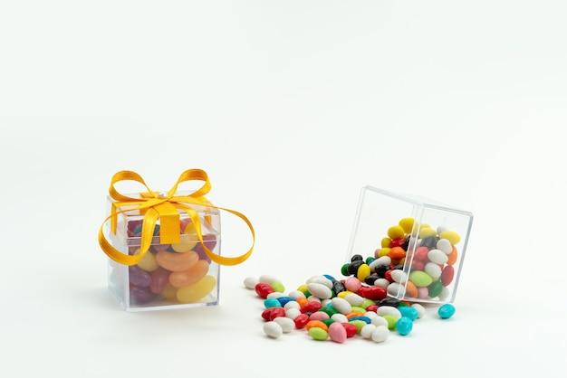 Uma vista frontal de doces coloridos com geleias em branco, cor açúcar doce