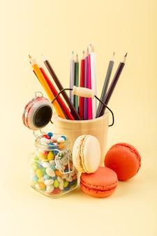 Uma vista frontal de doces coloridos com macarons franceses e lápis multicoloridos