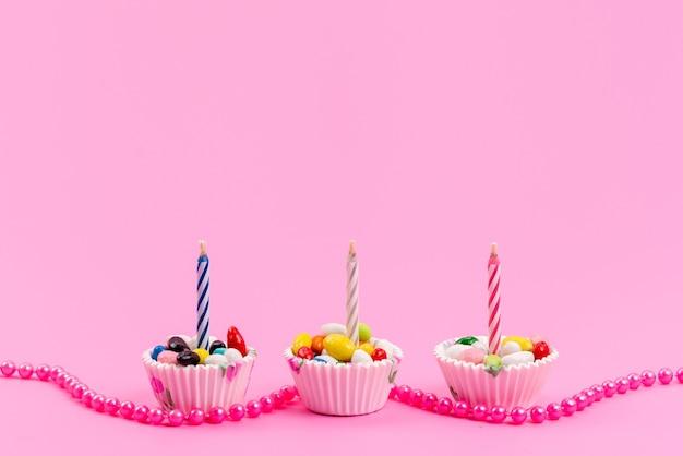 Uma vista frontal de doces coloridos dentro de pacotes de papel branco com vela rosa, confeitaria açucarada