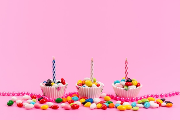 Uma vista frontal de doces coloridos dentro de pacotes de papel branco com velas oon rosa, doce de açúcar
