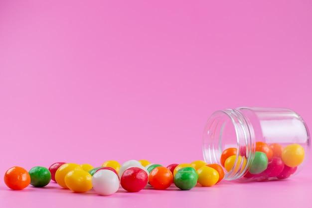 Uma vista frontal de doces coloridos dentro e fora da lata pequena em rosa, cor doce açúcar