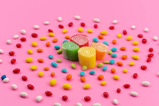 Uma vista frontal de doces coloridos e geléias isoladas em rosa, cor de açúcar doce