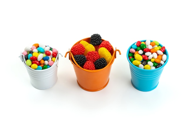 Uma vista frontal de doces coloridos junto com geleias no arco-íris de cor branca