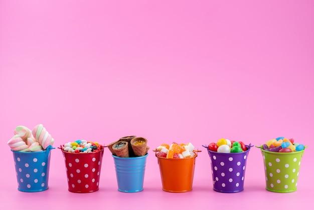 Uma vista frontal de doces diferentes, como doces confitures marmeladas dentro de cestas na cor rosa, açúcar doce