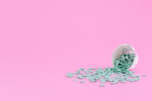 Uma vista frontal de doces verdes dentro e fora do pacote de papel na cor rosa doce