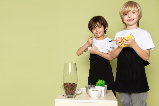 Uma vista frontal de dois meninos bonitos adoráveis em camisetas brancas, preparando a bebida do café no chão colorido de pedra