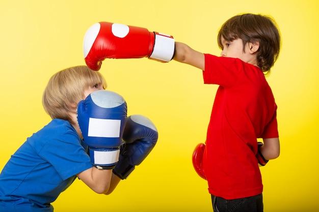 Uma vista frontal de dois meninos brigando em luvas de boxe na parede amarela
