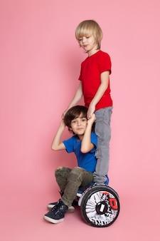 Uma vista frontal de dois meninos em camisetas vermelhas e azuis, montando segway no espaço rosa
