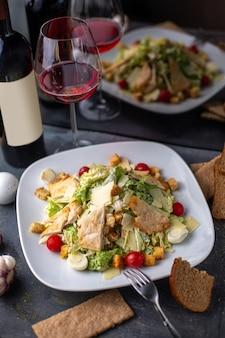 Uma vista frontal de frango fatiado com verduras de legumes dentro de um prato branco salgado salpicado junto com batatas fritas de vinho tinto nos pratos de mesa cinza