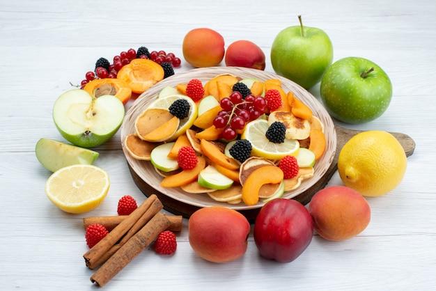 Uma vista frontal de frutas frescas cortadas aveludadas com canela e frutas inteiras na mesa de madeira e fundo branco.