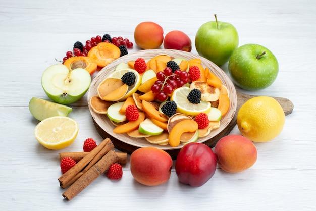 Uma vista frontal de frutas frescas fatiadas coloridas e suaves com canelas na mesa de madeira e fundo branco.