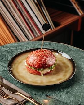 Uma vista frontal de hambúrguer frito com legumes frescos e carne no prato redondo