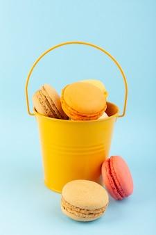 Uma vista frontal de macarons franceses deliciosos e assados dentro de uma cesta