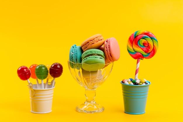 Uma vista frontal de macarons franceses junto com balas e pirulitos dentro de baldes em doces doces de confeitaria amarelos