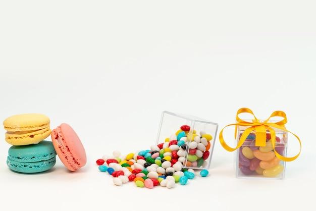 Uma vista frontal de macarons franceses junto com doces coloridos na cor do bolo de biscoito branco