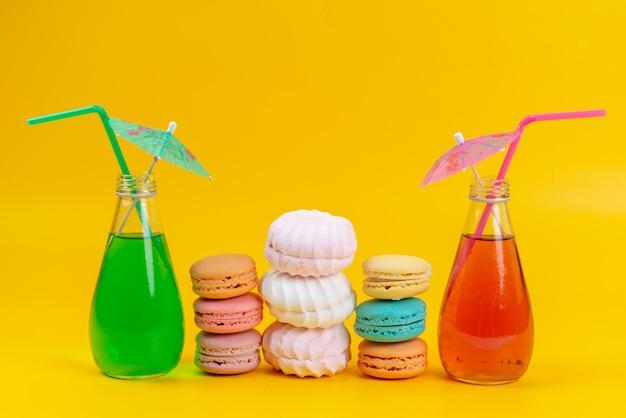 Uma vista frontal de macarons franceses junto com merengues e drinks coloridos em bolachas amarelas