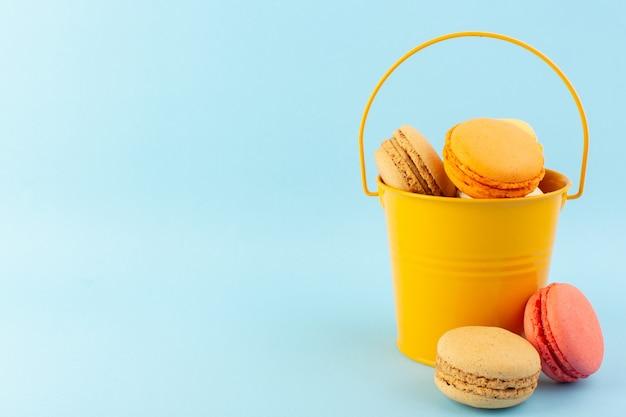 Uma vista frontal de macarons franceses multicoloridos dentro de um balde na mesa azul