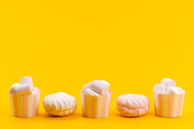 Uma vista frontal de marshmallows brancos dentro de pacotes de papel junto com merengues brancos em amarelo