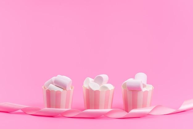 Uma vista frontal de marshmallows brancos dentro de pacotes de papel rosa isolados em rosa