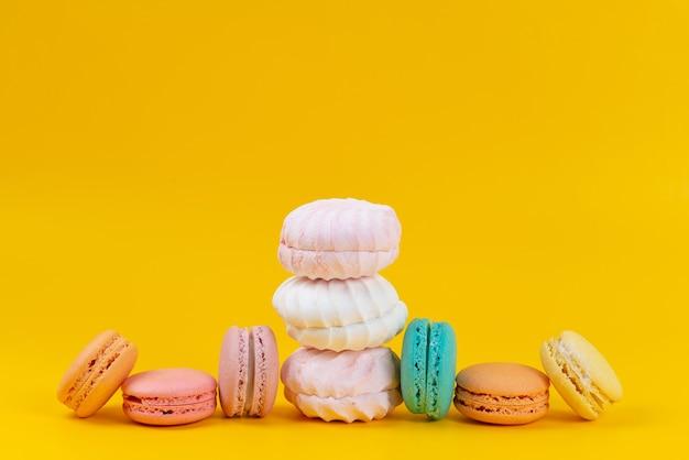 Uma vista frontal de merengues e macarons deliciosos assados em amarelo, biscoito de bolo de cor doce